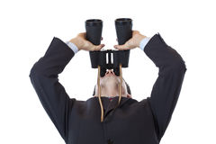 Curious businessman holds binoculars up to the sky Royalty Free Stock Photos