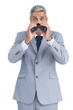 Curious businessman observing with binoculars. Curious businessman on white background observing with binoculars Stock Photography
