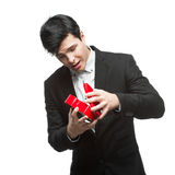 Curious businessman opening gift Royalty Free Stock Photos