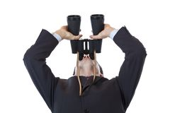 Curious businessman turns binoculars up to the sky Stock Photography