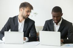 Free Curious Caucasian Worker Looking At African American Colleague W Stock Photos - 117972373