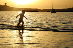 A toddler running though the water during a vibrant gold sunset Royalty Free Stock Photo