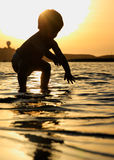 Baby boy playing in the ocean during sunset Stock Images