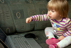 Curious child with computer. Young female child pointing a finger at a computer keyboard Royalty Free Stock Images