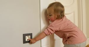 Curious child playing with electric plug