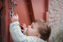 Curious child playing with keys outdoors stock photo
