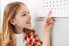 Curious child reading letters from doctors chart. Cool thing. Intelligent beautiful lovely girl pointing at something on the table while visiting ophthalmologist royalty free stock photos