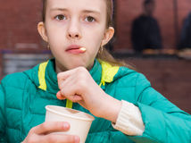 Curious child staring ahead while eating ice cream Royalty Free Stock Photos