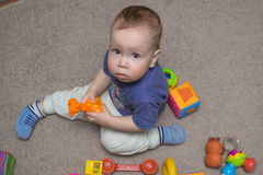 Curious child studying toys Stock Images