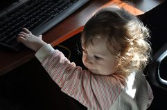Cute baby girl playing with keyboard stock image