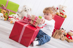 Curious child: young girl opening Christmas present with teddy b. Ears in background - nosy Stock Photography