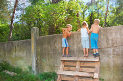 Curious children spying over the fence Stock Photography