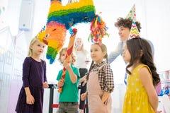 Curious children standing around pinata stock photo