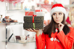 Curious Christmas Girl with Presents in Gift Shop Royalty Free Stock Images