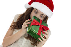 Curious Christmas woman peeking into gift box Royalty Free Stock Image