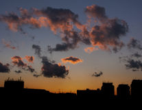 Curious clouds at sunset. Curious colorful clouds on city scape background at sunset Stock Images
