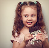 Curious cute kid girl eating dark chocolate and looking fun. Clo Stock Photos