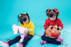 Curious dark-haired kids dealing with toys on their knees stock image
