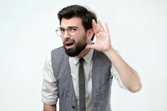 Curious or deaf man placing hand on ear asking someone to speak up or listening to bad news. Closeup portrait of curious or deaf man placing hand on ear asking stock photos