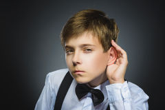 Curious Disappointed boy listens. child hearing something, parents talk, hand to ear gesture isolated grey Royalty Free Stock Photo