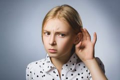 Curious Disappointed girl listens. Closeup portrait child hearing something, parents talk, hand to ear gesture  Royalty Free Stock Photo