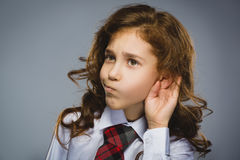Curious Disappointed girl listens. Closeup portrait child hearing something, parents talk, hand to ear gesture isolated. Grey background. Human face expression royalty free stock images