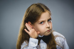 Curious Disappointed girl listens. Closeup portrait child hearing something, parents talk, hand to ear gesture isolated. Grey background. Human face expression stock image