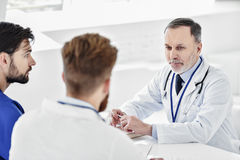 Curious doctors speaking at round table Stock Photos