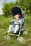 Curious European girl in a pink scarf in a blue stroller for a walk. Baby girl 9 months carefully. Focused smart look, small child. Curious European girl in a stock photos