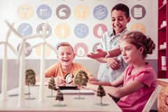 Contented African American boy laughing and pointing on model. Curious experimenters. Contented African American boy laughing and pointing on model of wind royalty free stock photo