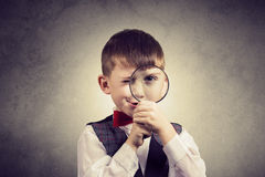 Curious Exploring little boy with magnifying glass, on yellow ba Royalty Free Stock Photos