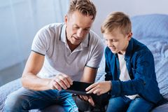 Curious father and son inspecting new VR headset. Brand new device. Cheerful curious father and his little son sitting on the bed and inspecting their new VR Stock Photography