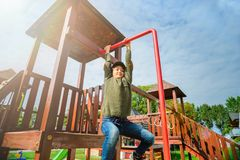 Curious fearless little girl climbing on playground alone in sunny weather Stock Photos