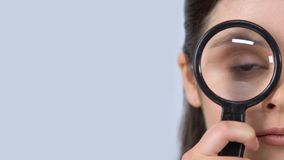 Curious female looking through magnifying glass, studying information, survey. Stock footage stock video footage