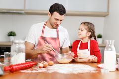 Curious female pretty child helps her father who mixes eggs, sit at kitchen, have pleasant conversation, enjoy stock photos