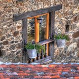 Curious flowerpots in a window. Curious window flowerpots in a mountain village royalty free stock photography
