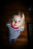 Curious girl. Curious little girl looking up into camera wearing a striped shirt Royalty Free Stock Image