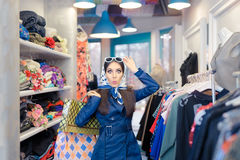 Curious Girl in Blue Trench Coat and Sunglasses Shopping Royalty Free Stock Image