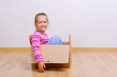 Curious girl in cardboard box Stock Photos