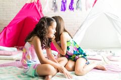 Curious Girl Gossiping In Friend`s Ear At Home. Curious girl gossiping in best friend`s ear while sitting on duvets at home royalty free stock photo