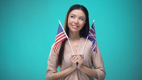 Curious girl holding Great Britain and USA flags, language difference, education. Stock footage stock footage