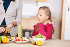 Curious Girl Looking At Fruit Salad In Kitchen Stock Photography