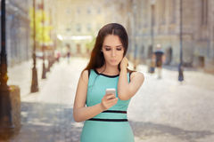 Curious Girl Looking at Her Phone. Portrait of a urban young woman checking out her phone Royalty Free Stock Photos