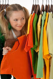 Curious girl looking out of the clothes rack. In a store, choosing what to buy Royalty Free Stock Photos