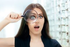 Funny Woman with Magnifying Glass Ready For Eye Exam. Curious girl looking for the perfect pair of glasses Stock Photo