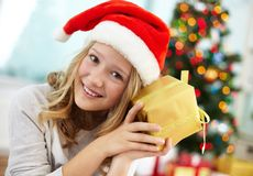Curious girl. Portrait of curious girl holding giftbox and guessing what is inside Stock Photos
