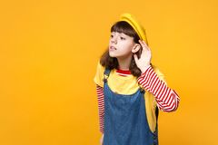Curious girl teenager in french beret, denim sundress looking aside, eavesdrop with hearing gesture isolated on yellow. Wall background. People sincere emotions royalty free stock image