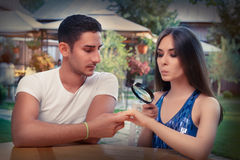 Curious Girl Testing Engagement Ring from Boyfriend with Magnifier Stock Photography