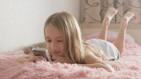 Curious girl using phone apps looking at cellphone device sitting on bed, child and gadget concept.