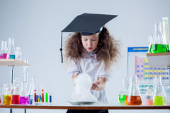 Curious girl watching result of experiment in lab Royalty Free Stock Images